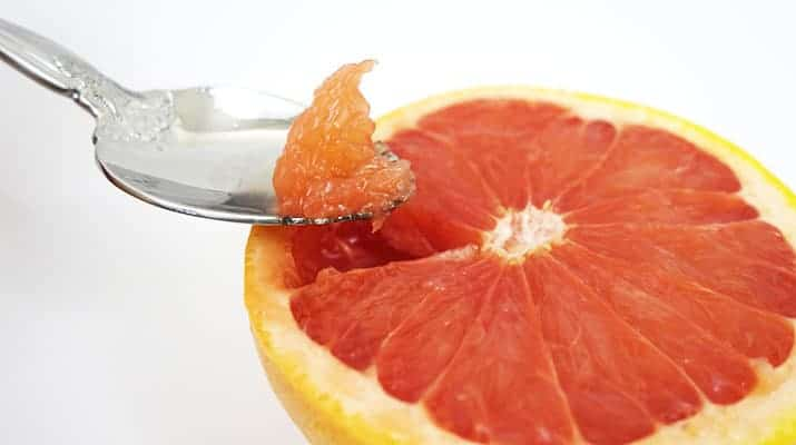 Lifting the grapefruit triangle section out of the skin
