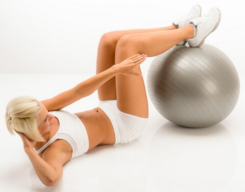 Woman doing sit-ups on fitness ball white